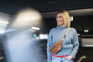 Smiling young woman in a parking garage - DIGF09013