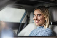 Portrait of smiling young woman driving a car - DIGF09019
