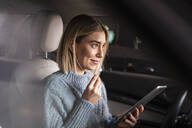 Smiling young woman with tablet and earphones in a car - DIGF09022