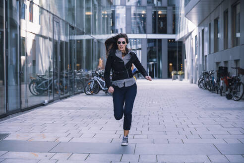 Woman with sunglasses running away - DHEF00002