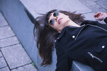 Middle aged businesswoman with sunglasses, lying on concrete bench - DHEF00008