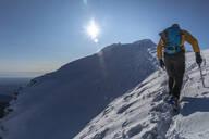 Mountaineer hiking on snowy mountain, Lecco, Italy - MCVF00088