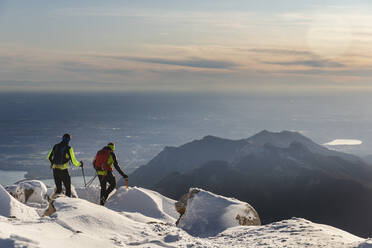 Mountaineers hiking on snowy mountain, Lecco, Italy - MCVF00091