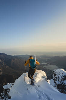 Mountaineer reaching the top of a snowy mountain enjoying the view, Lecco, Italy - MCVF00094