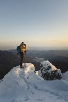 Mountaineer standing on top of a snowy mountain enjoying the view, Lecco, Italy - MCVF00097