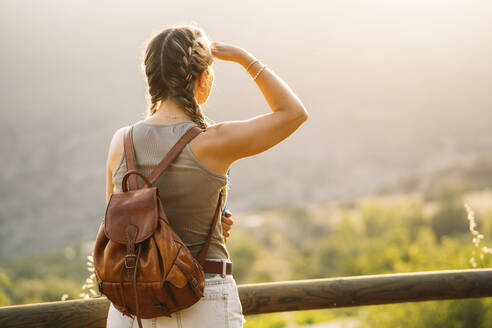 Woman with leather backpack looking at view - MPPF00334