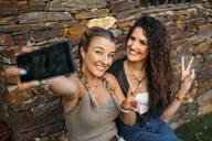 Two happy women sitting at a stone house taking a selfie - MPPF00355