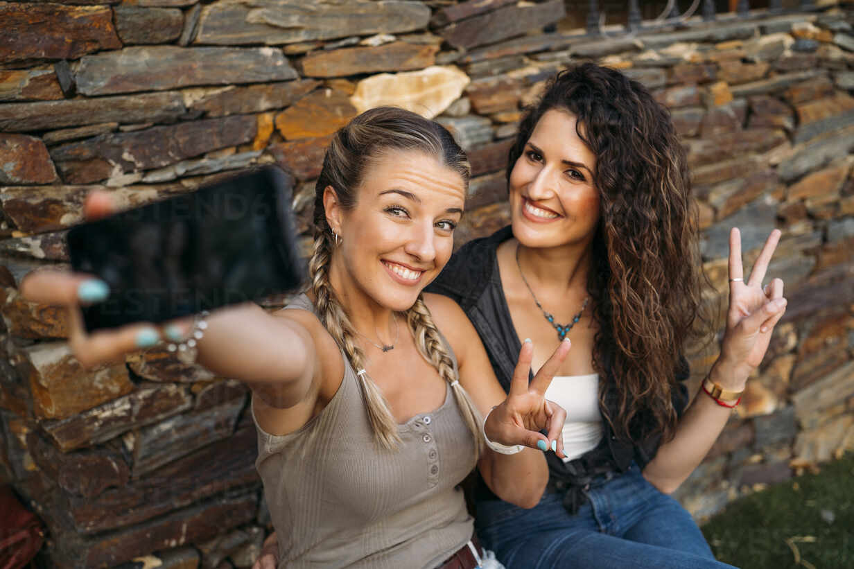 Two happy women sitting at a stone house taking a selfie - MPPF00355 - Manu Padilla Photo/Westend61