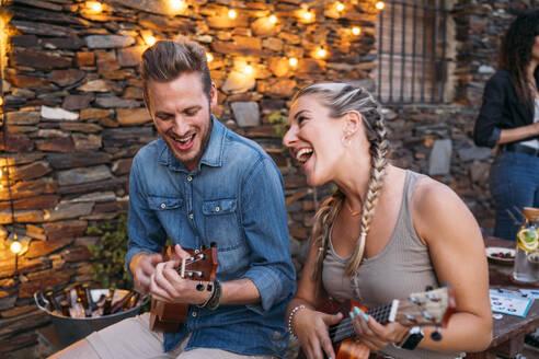 Happy couple playing ukulele outdoors at a stone house at dusk - MPPF00364