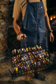 Close-up of man holding grill with meat and vegetable skewers - MPPF00370
