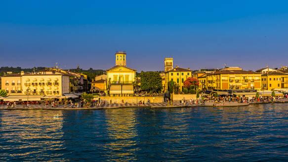 Italy, Province of Verona, Lazise, Promenade of lakeshore city at dusk - MHF00511