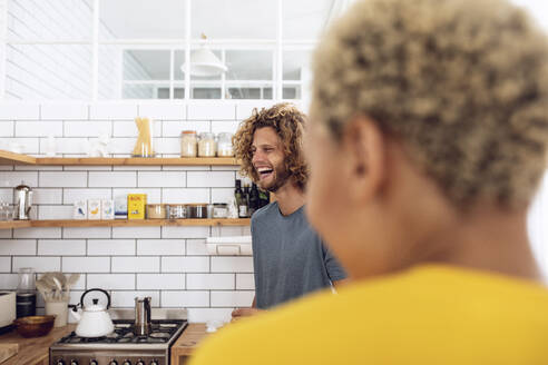 Laughing man with woman in the kitchen at home - MCF00380