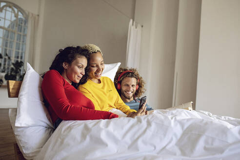 Happy friends relaxing in bed at home with smartphone - MCF00386