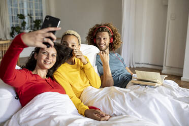 Happy friends relaxing in bed at home with smartphone - MCF00389