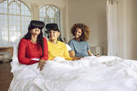 Happy friends having fun with VR glasses in bed at home - MCF00392