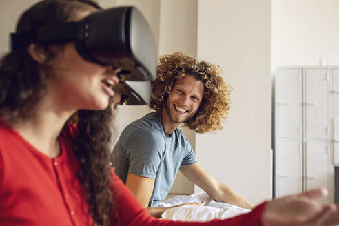 Happy friends having fun with VR glasses in bed at home - MCF00395