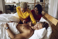 Young woman writing on chest of sleeping friend in bed at home - MCF00401