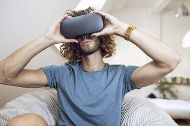 Young man wearing VR glasses at home - MCF00404