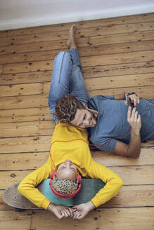 Young couple lying on the floor at home relaxing - MCF00413