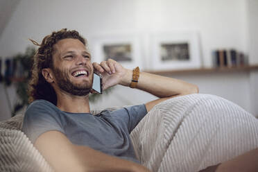 Laughing young man relaxing in beanbag at home talking on the phone - MCF00416
