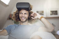 Portrait of smiling young man wearing VR glasses at home - MCF00419