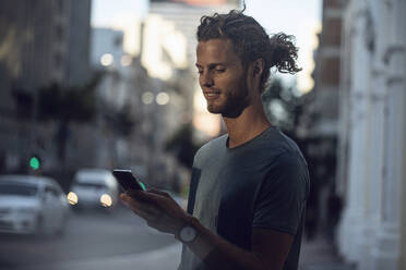 Confident young man using smartphone in the city - MCF00425