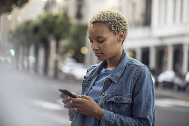 Young woman using smartphone in the city - MCF00428