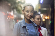 Portrait of confident young woman with her friend in the city - MCF00434
