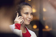 Portrait of smiling young woman on the phone - MCF00437