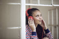 Young woman at the window listening to music - MCF00440