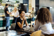 two girlfriends meeting and talking in a bistro - SODF00416