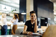 Young woman sitting in bistro, reading magazine - SODF00419