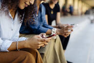 Three women sitting on steps in a row, using smartphones - SODF00431