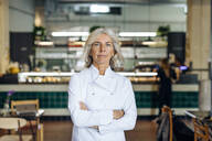 Proud business owner standing in her bistro with arms crossed - SODF00437