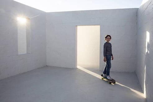Little girl in empty room, standing on skateboard - MCF00445