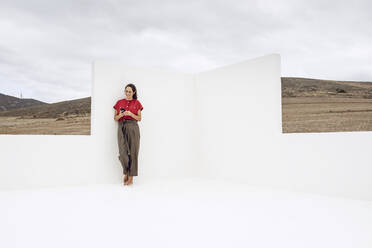 Businesswoman with smartphone, standing by white wall - MCF00448