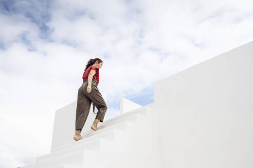 Barefooted businesswman climbing white stairs under cloudy sky - MCF00463