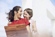 Girl watching mother using laptop with wooden cover - MCF00472