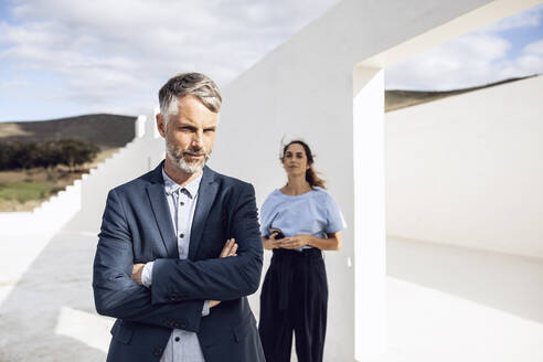Businessman standing with arms crossed, woman leaning on white wall - MCF00478