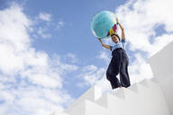Woman standing on white stairs, carrying inflatable globe - MCF00484