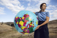 Mature woman holding inflatable globe, looking confident - MCF00487