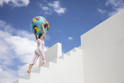 Little girlclimbing  white stairs, carrying inflatable globe - MCF00490
