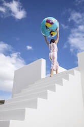 Little girlclimbing  white stairs, carrying inflatable globe - MCF00493