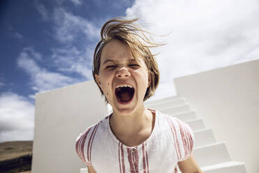Girl with windswept hair, screaming out loud - MCF00496