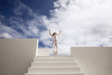 Little girl on top of stairs jumping for joy - MCF00499