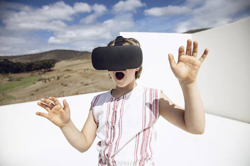Girl looking through VR goggles in open space - MCF00508