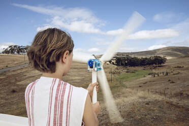 Girl looking at small wind turbine on white wall - MCF00511