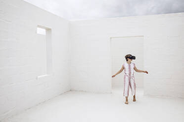 Little girl discovering empty space with VR goggles - MCF00514