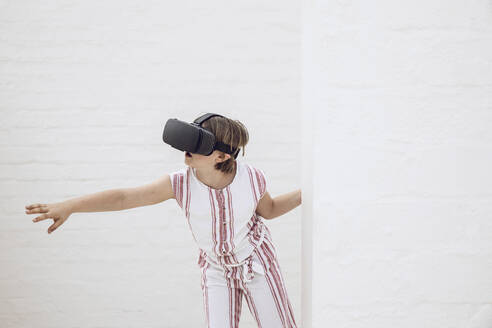 Little girl discovering empty space with VR goggles - MCF00517