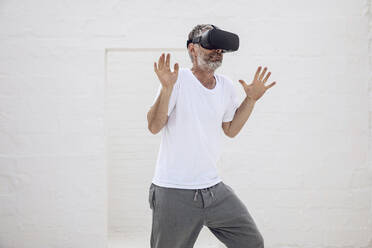 Mature man discovering empty space with VR goggles - MCF00520